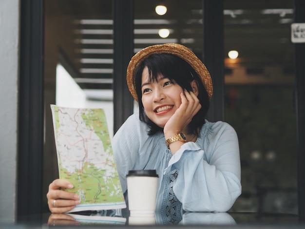 魅力的なアジア人地図を押しながらコーヒーショップでコーヒーを飲みます。