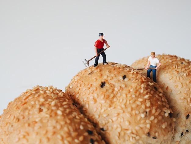 Закройте миниатюрных людей, многие из рабочих человек, работающих на фоне цельнозерновой хлеб