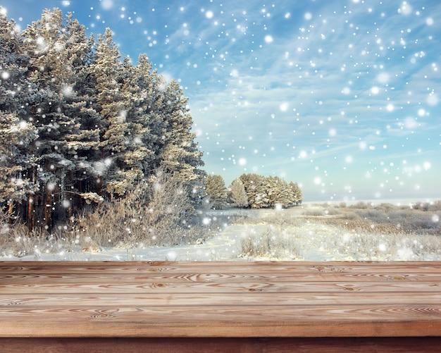 冬の風景の背景に木製のテーブル。