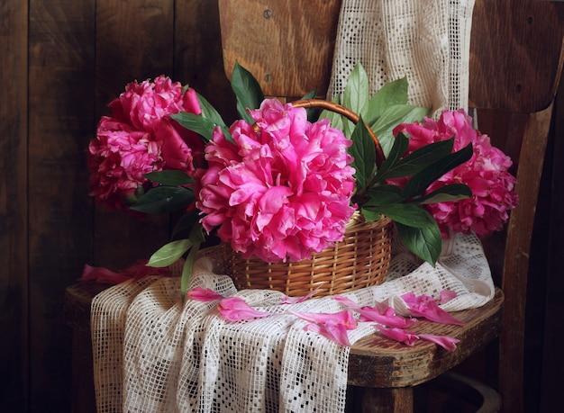 Ретро натюрморт с рушится розовые пионы. цветы в корзине.