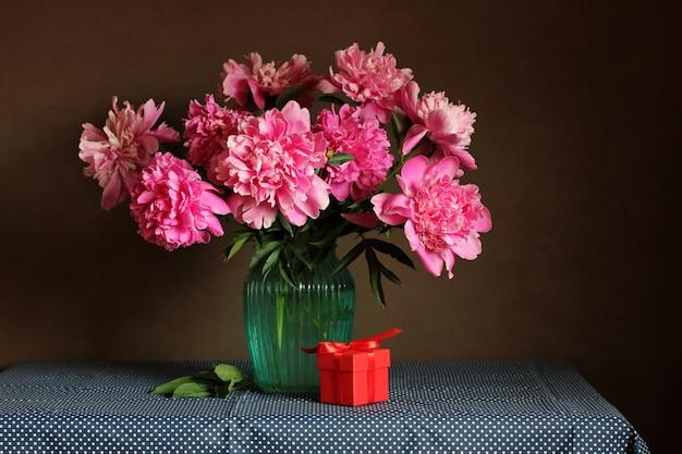 ピンクの牡丹の花束とテーブルの上の贈り物。祝日おめでとうございます。