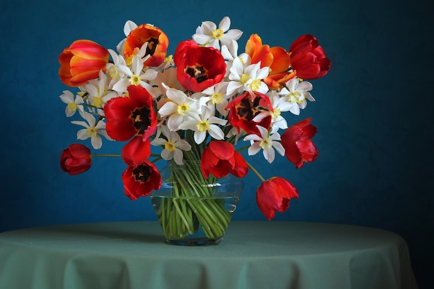 青い水仙とチューリップの花束のある静物。