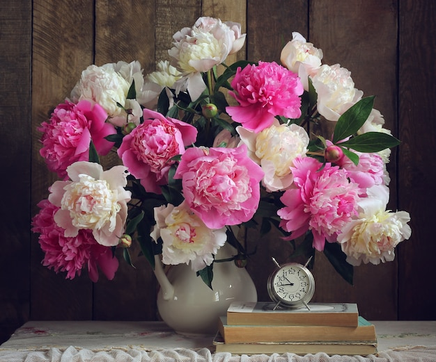 白いピッチャー、書籍、目覚まし時計の牡丹の花束。