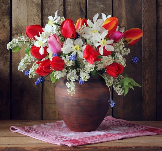粘土の水差しの水仙とチューリップの春の花束。素朴なスタイルの花束のある静物。