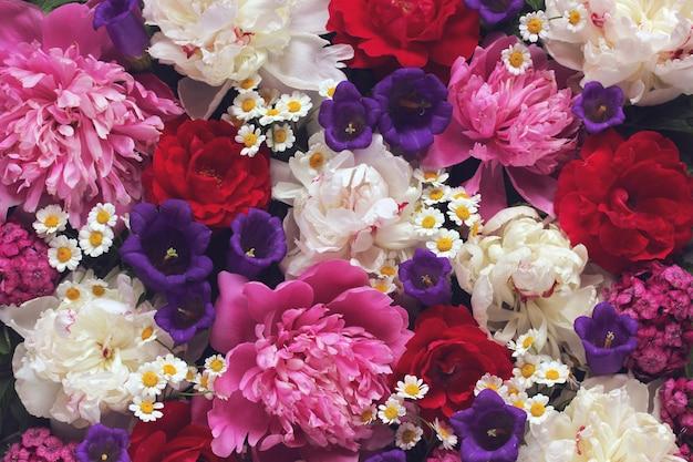 美しい花の背景。庭の花、トップビュー。牡丹、ヒナギク、バラ。