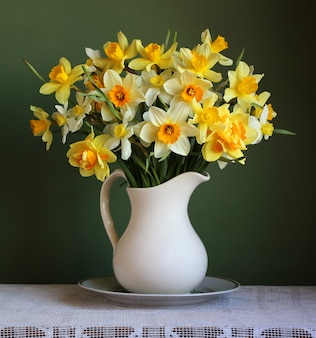 白い水差しの黄色い庭の水仙の花束