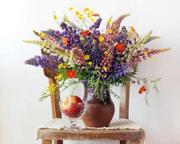 ルピナスと水差しの中のキンポウゲと明るい背景に椅子の上の花瓶にリンゴのある静物ブーケ。