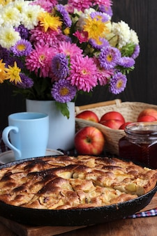 Яблочный пирог, запеченный в домашних условиях. еда натюрморт в деревенском стиле. десерт и букет из культурных цветов.