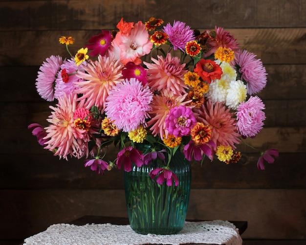 花瓶の秋の庭の花の緑豊かな花束。アスターとダリア