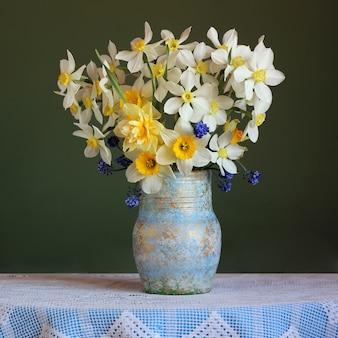 レースのテーブルクロスをかけたテーブルの上の黄色の水仙の花束。