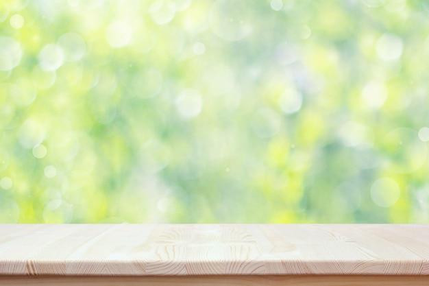 ボケ味を持つ春の背景をぼかしに空の木製のカウンタートップ。