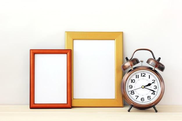 空白のゴールドフォトフレームとブロンズの目覚まし時計