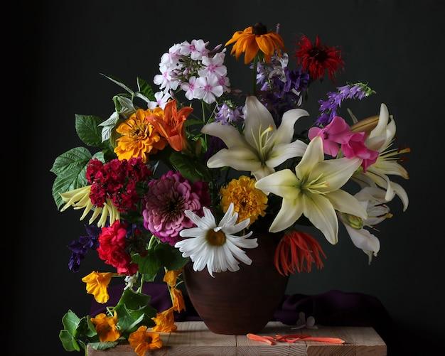 粘土の水差しの庭の花の緑豊かな花束。ユリ、フロックス、ヒナギクなど。