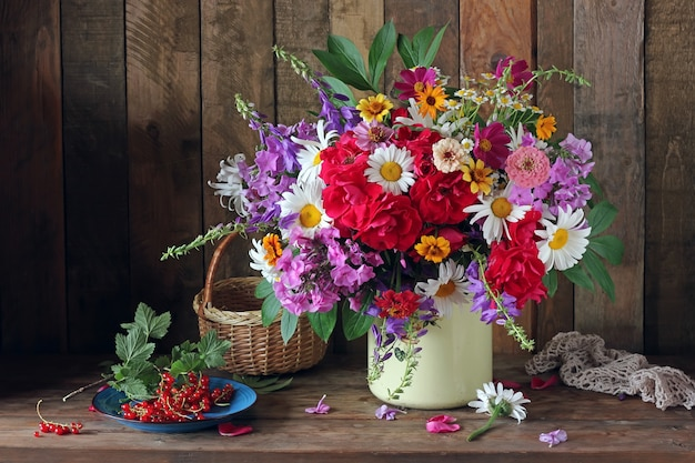 缶の中の庭の花と素朴な木製のテーブルの上の赤スグリの花束。