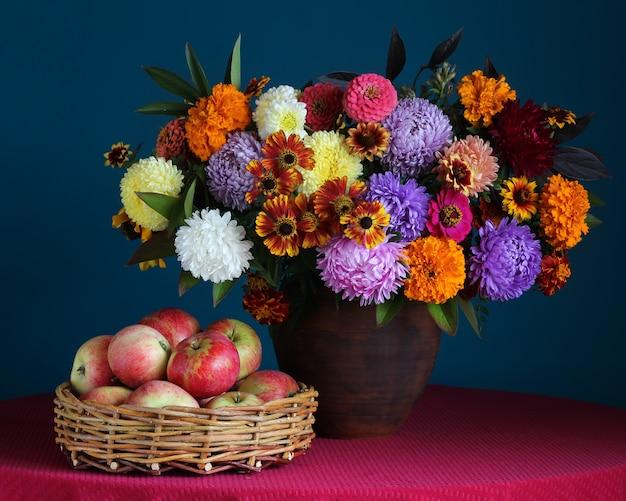 粘土の瓶の秋の花束とバスケットの赤いリンゴのある静物。