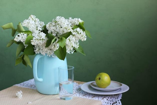 Цветущая белая сирень в кувшине, букет цветов в вазе.