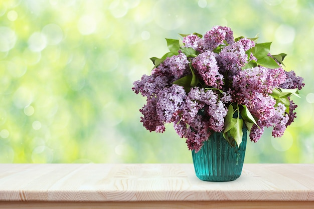 木製のテーブルの上のライラックの花束。ボケ味を持つ春背景をぼかした写真の花瓶に花。