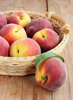 Спелые персики в корзине.