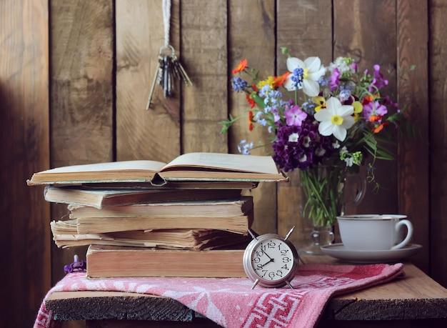 本、目覚まし時計、花束のレトロな静物