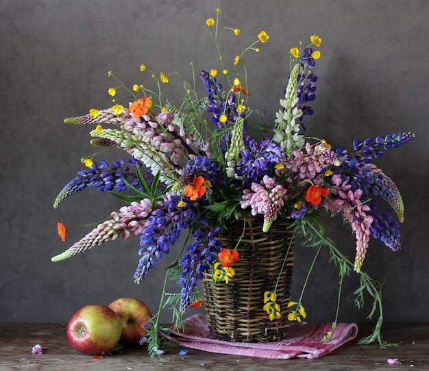 タオルとリンゴのバスケットにルピナスとキンポウゲの花束、夏の静物画。