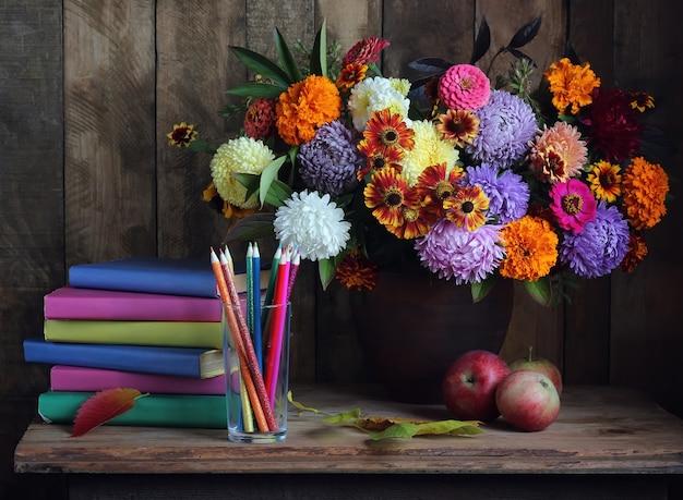 Букет, стопка книг и яблок на столе. обратно в школу. день учителя. первое сентября.