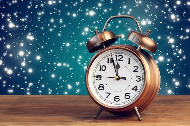 Бронзовый ретро будильник в двенадцать часов на фоне летающего снега. полночь, полдень. минуты до нового года.
