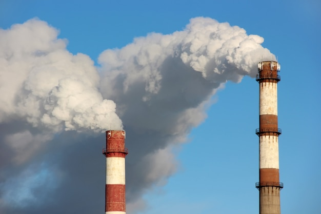 Густые клубы дыма или пара из двух труб. понятие экологии, загрязнения окружающей среды.