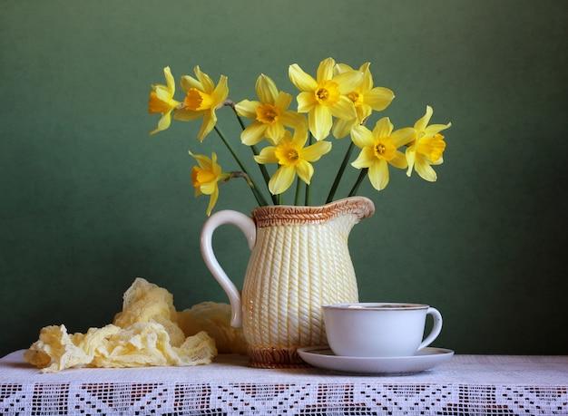 春の花瓶の中の黄色い水仙の花束と古いマグカップのある静物。