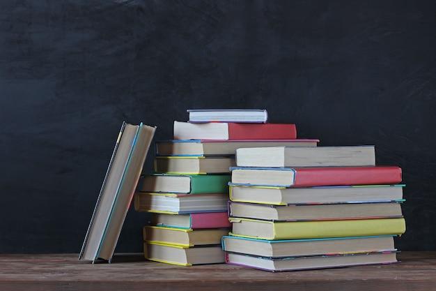 学校の黒板に本のスタック。学校に戻る。テーブルの上の色付きの表紙の教科書。