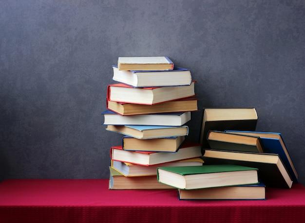 赤いテーブルクロスとテーブルの上の色のカバーの本のスタック。本のある静物