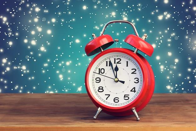 Красный ретро будильник в двенадцать часов на фоне летающего снега. полночь, полдень. минуты до нового года.