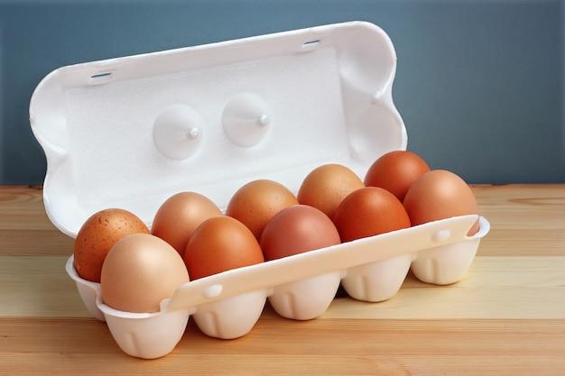 Десять куриные коричневые яйца в белом пенопластовом пакете на деревянный стол.