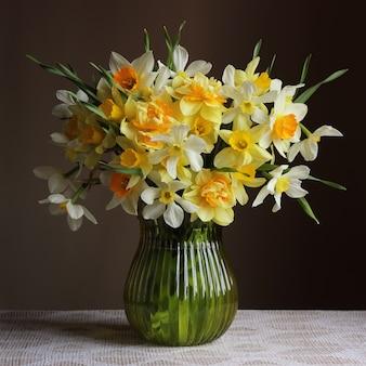 暗闇の中でガラスの花瓶に黄色の水仙の花束