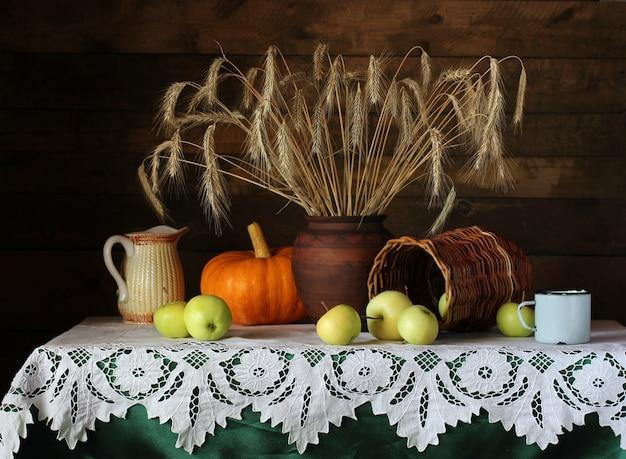 ライ麦小穂、リンゴとオレンジ色のカボチャのテーブルの上の素朴なスタイルの静物