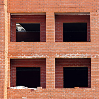 Строительство нового многоэтажного дома из красного кирпича.