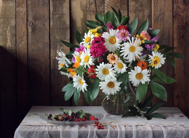 夏の花束とテーブルクロスをテーブルの上の果実のある静物