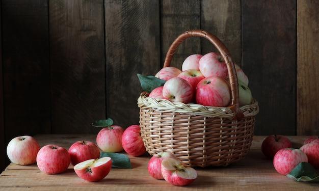 木製のテーブルの上のバスケットにリンゴ。