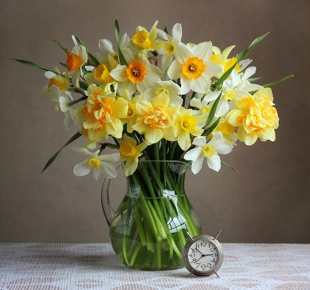 透明な水差しと白いテーブルクロスとテーブルの上のレトロな目覚まし時計で黄色の水仙の花束。静物。