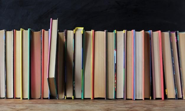 学校の黒板を背景にした棚の上の色のついた表紙の本。