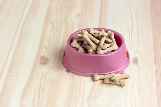 ピンクのプラスチック製のボウルに骨の形をしたビスケット