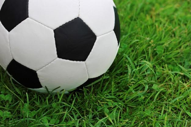 緑の芝生の上のサッカーの黒と白のボールのクローズアップ。
