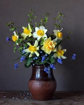 粘土の水差しで水仙の花束
