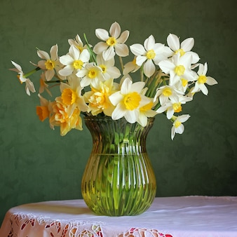 レース付きの白いテーブルクロスをかけたテーブルの上のガラスの花瓶に水仙の花束のある静物
