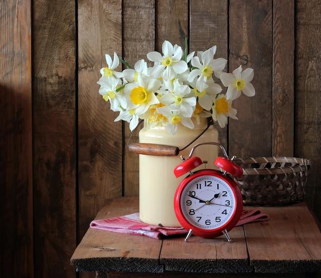 水仙の花束と赤い目覚まし時計のある静物。