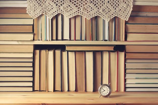 Полка с книгами. много книг, будильник и кружевная салфетка на деревянной полке.