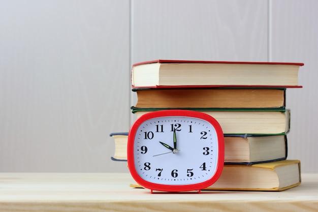 時計と本テーブルの上の教科書のスタック。