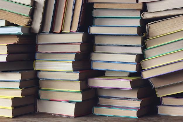 本からの背景。棚のクローズアップの本の山。としょうかん。学校に戻る。