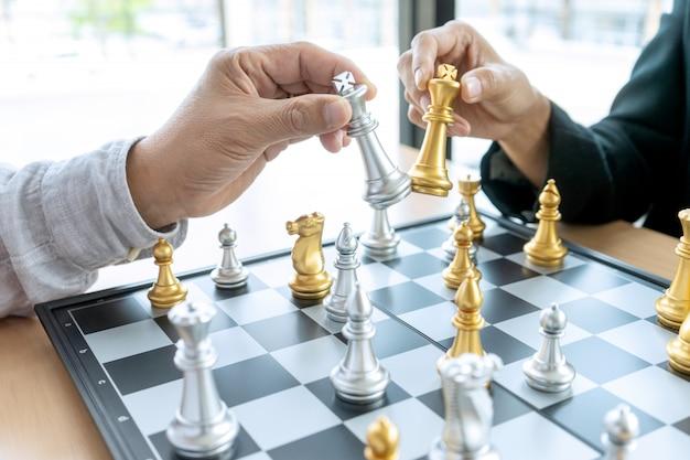 ビジネスマン思考と彼の手にチェス王を握る、