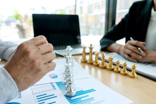 ビジネスマンは、マーケティングの職場でチェスをする