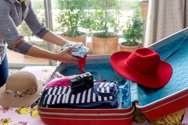 Женщина упаковывает багаж